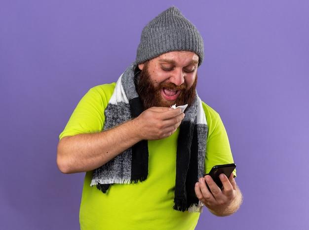 Hombre barbudo insalubre con sombrero y bufanda caliente alrededor del cuello sintiendo terrible sufrimiento de gripe mirando el teléfono móvil que va a estornudar de pie sobre la pared púrpura