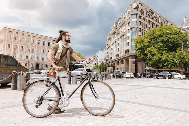 Hombre barbudo inteligente que usa una bicicleta mientras evita los atascos de tráfico en la ciudad
