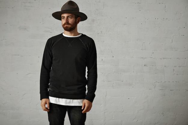 Hombre barbudo joven de aspecto triste en sudadera de algodón de manga larga negra en blanco y sombrero de montaña de fieltro con paredes de ladrillo blanco