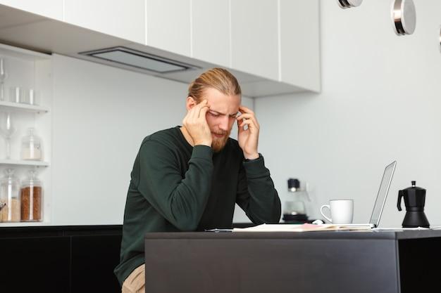 Hombre barbudo joven cansado con dolor de cabeza sentado en la cocina con ordenador portátil.