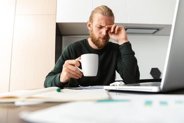 Hombre barbudo joven cansado sentado en la cocina tomando café con ordenador portátil.