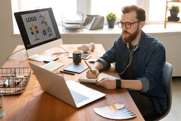 Hombre barbudo joven concentrado escuchando música en auriculares y haciendo bocetos en el bloc de notas mientras trabaja en un dibujo digital