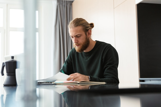 Hombre barbudo joven concentrado sentado en casa usando la computadora portátil trabajar con documentos.