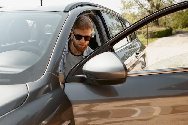Hombre barbudo joven confiado en gafas de sol de moda en coche.