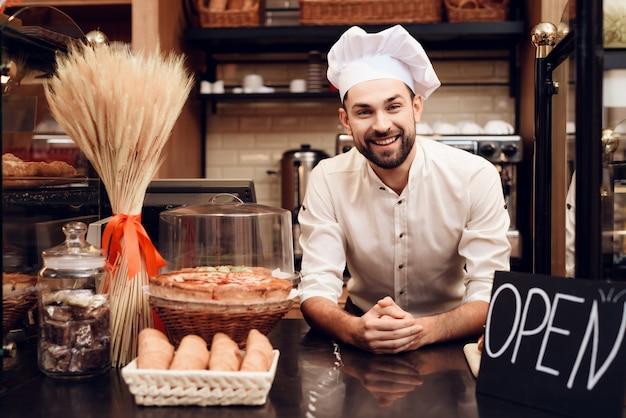 Hombre barbudo joven en el delantal que se coloca en panadería.