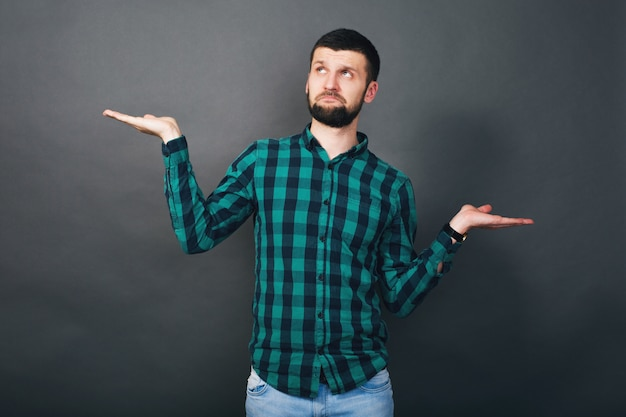 Hombre barbudo joven guapo hipster sosteniendo las manos arriba pregunta de evaluación, camisa a cuadros verde, fondo gris