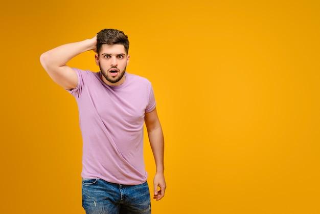 Hombre barbudo joven que lleva a cabo su cabeza sorprendida aislada sobre fondo amarillo
