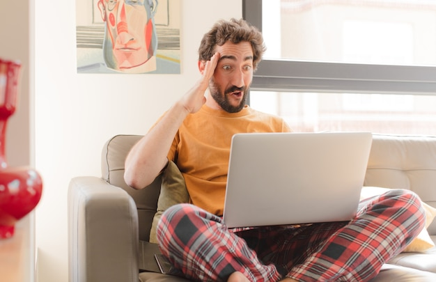 Hombre barbudo joven que parece feliz asombrado y sorprendido sonriendo y dándose cuenta de buenas noticias increíbles e increíbles y sentado con una computadora portátil