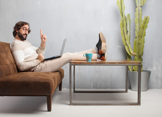 Hombre barbudo joven que se sienta en un sofá de cuero en una sala de estar del vintage