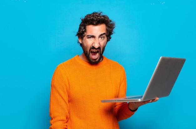 Hombre barbudo joven que sostiene una computadora portátil. concepto de redes sociales