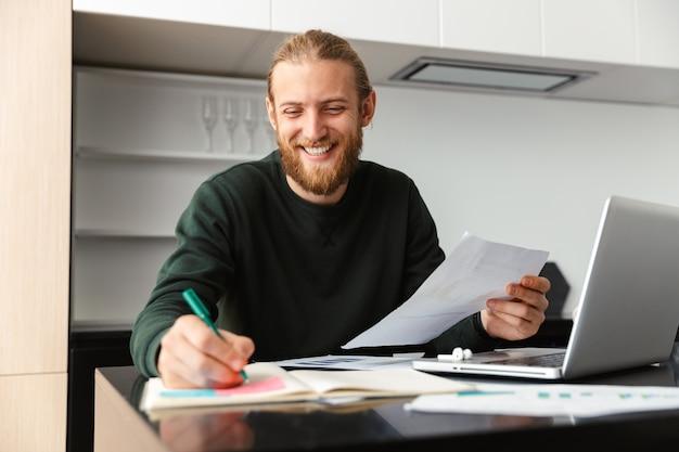 Hombre barbudo joven sentado en la cocina escribiendo notas en documentos con ordenador portátil.