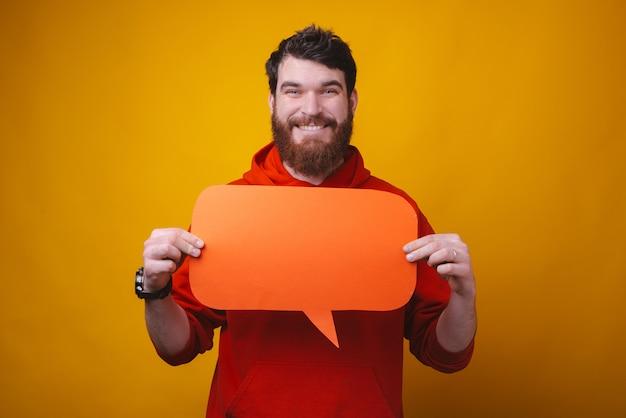 El hombre barbudo joven sonriente está llevando a cabo un discurso de la burbuja delante de su pecho en espacio amarillo.