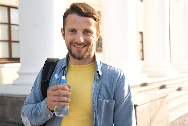 Hombre barbudo joven sonriente que sostiene la botella de agua y que mira la cámara
