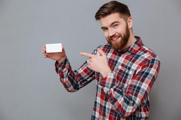 Hombre barbudo joven sonriente que sostiene la tarjeta de visita en blanco