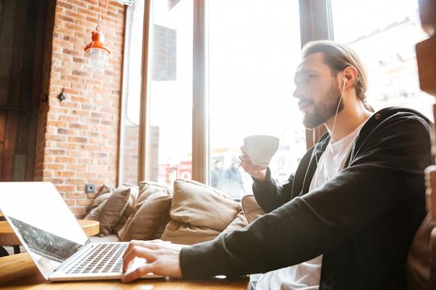 Hombre barbudo con laptop tomando café en la cafetería