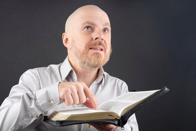 Hombre barbudo leyendo la biblia señala con el dedo el texto y mira hacia arriba