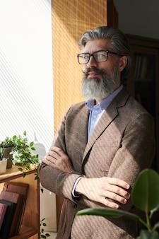 Hombre barbudo maduro confiado con traje elegante y anteojos de pie con los brazos cruzados