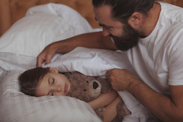 Hombre barbudo maduro descansando en casa con su pequeña hija
