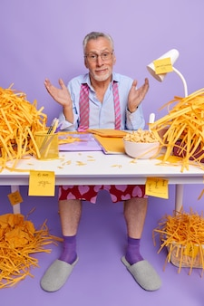 Hombre barbudo maduro no sabe cómo preparar informes financieros se ve con expresión despistada trabajo en la oficina en casa usa ropa doméstica tiene mucho trabajo por hacer no puede decidir por qué empezar.