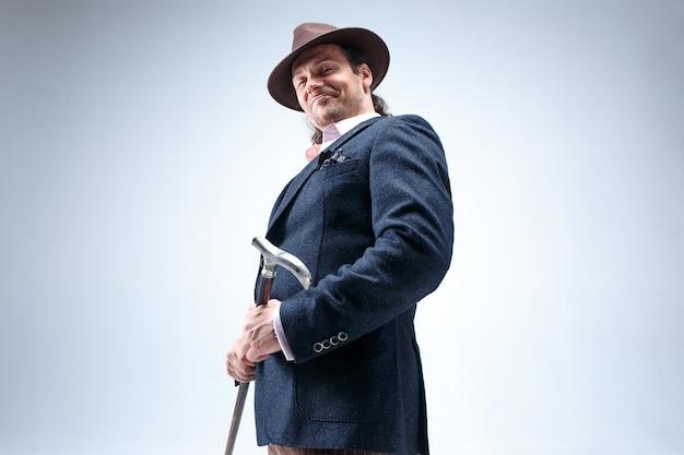 El hombre barbudo maduro con traje y sombrero con bastón. aislado en un fondo gris de estudio.