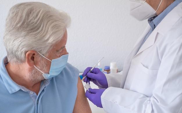 Hombre barbudo con mascarilla quirúrgica vacunándose, covid-19. concepto de vacunación por coronavirus