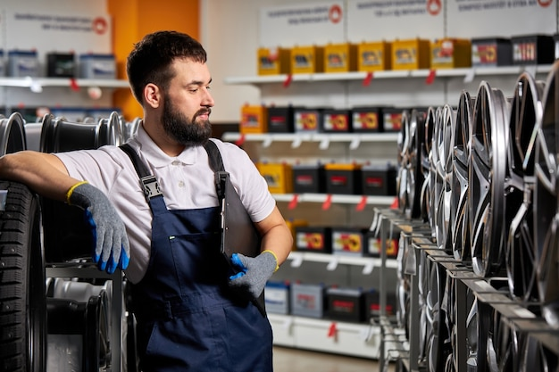 Hombre barbudo mecánico reparador examinando llantas de coche, comprobando el surtido en su tienda, en el lugar de trabajo, vistiendo uniforme