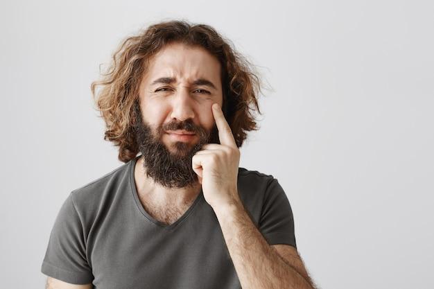 Hombre barbudo del medio oriente molesto miserable llorando, mostrando lágrima