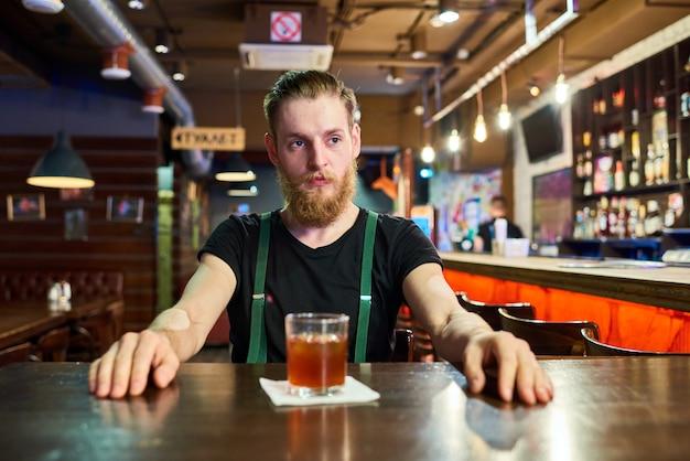 Hombre barbudo a la mesa en el pub