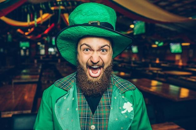 Hombre barbudo mira y grita. él es feliz. guy está solo en el pub.