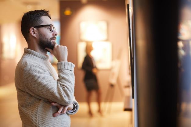 Hombre barbudo mirando pinturas en la galería de arte