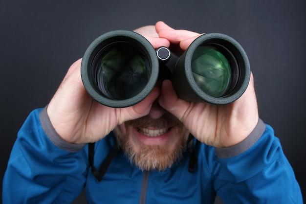 Hombre barbudo mirando a través de binoculares sobre fondo gris
