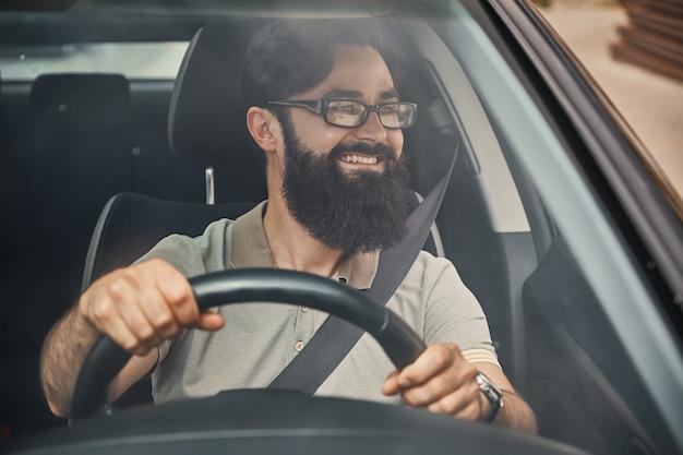 Un hombre barbudo moderno conduciendo un automóvil