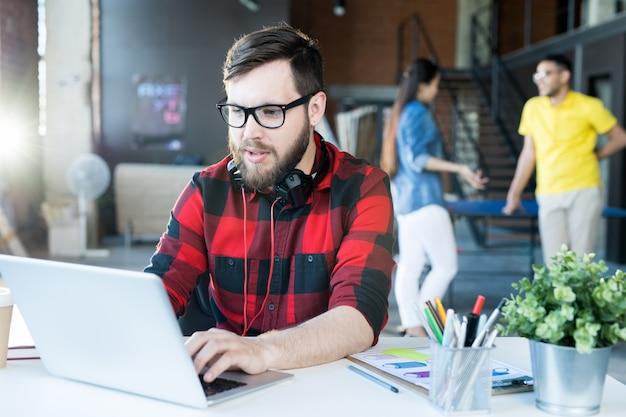 Hombre barbudo moderno usando laptop en espacio de coworking