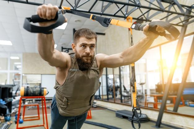 Hombre barbudo musculoso vestido con chaleco blindado pesado militar haciendo ejercicios