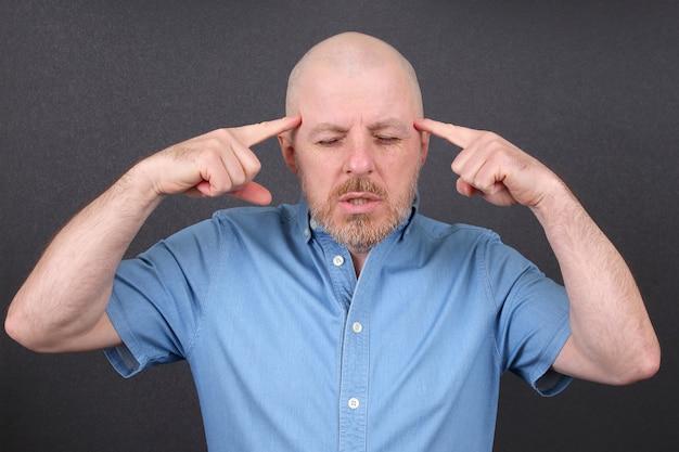 El hombre barbudo está muy estresado emocionalmente sosteniendo sus manos cerca de su cabeza