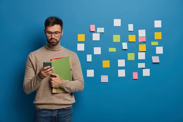 Hombre barbudo organizando sus tareas con notas adhesivas