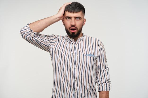 Hombre barbudo de pelo corto bastante joven desconcertado manteniendo la mano levantada en la cabeza y mirando perplejo con la boca abierta, aislada sobre la pared blanca