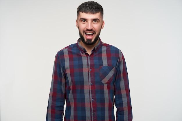 Hombre barbudo de pelo corto guapo joven emocionado mirando con los ojos muy abiertos y la boca abierta mientras está de pie sobre la pared blanca con las manos hacia abajo