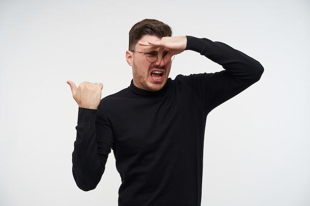 Hombre barbudo de pelo corto joven disgustado con gafas cerrando la nariz con los dedos mientras muestra disgusto y apunta hacia atrás con la mano levantada, posando en blanco