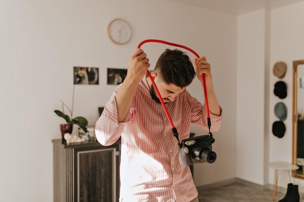 Hombre barbudo de pelo oscuro en camisa ligera con cámara. retrato de chico en la luminosa sala de estar sobre fondo de fotos de boda.