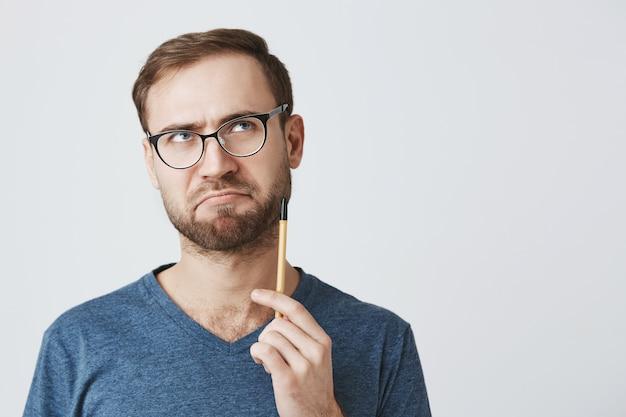 Hombre barbudo pensativo con gafas, sostenga el lápiz, pensando qué escribir