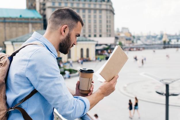 Hombre barbudo de pie cerca de la baranda con taza de café desechable mientras lee el libro