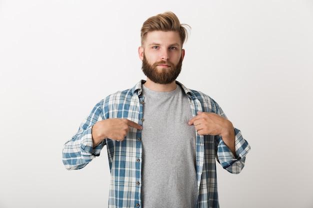 Hombre barbudo preocupado vestido con camisa a cuadros que se encuentran aisladas, señalando con el dedo a sí mismo
