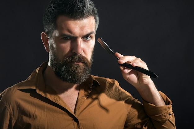 Hombre barbudo que se afeita en la barbería con el equipo de la barbería de la cuchilla de afeitar hombre guapo con barba
