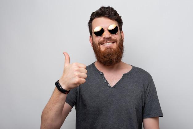 Hombre barbudo que muestra como gesto con el pulgar hacia arriba.