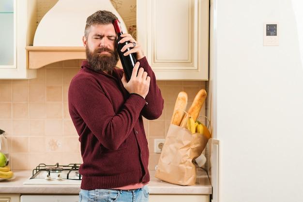 Hombre barbudo que sostiene la botella de vino en cocina. bolsa de supermercado con comida en la mesa. entrega de comida, productos a domicilio. tienda online de alimentos, productos y bebidas.