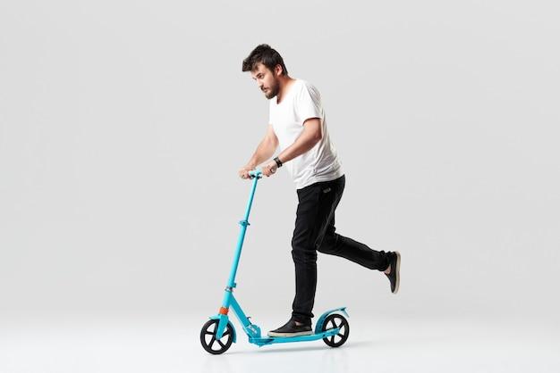 Hombre barbudo que sostiene el scooter eléctrico y lo conduce mientras se siente encantado