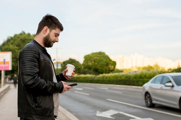 Hombre barbudo que sostiene la taza y el teléfono inteligente