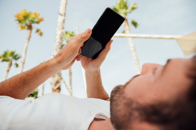 Hombre barbudo que sostiene el teléfono moderno