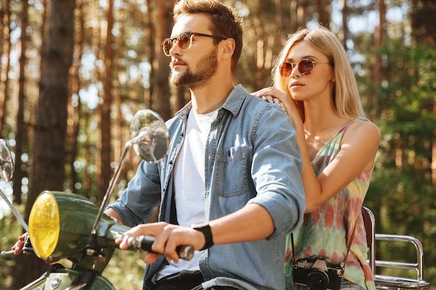 Hombre barbudo en scooter con novia al aire libre